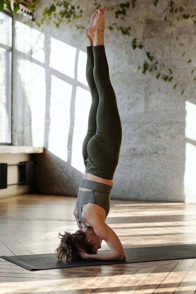 online yoga teacher doing a headstand pose